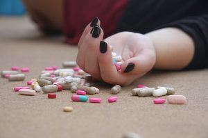 A hand on the floor with pills spilling out of it